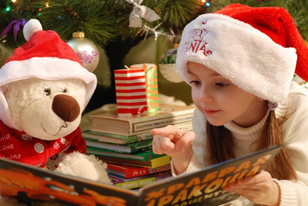 girl and teddy bear by christmas tree