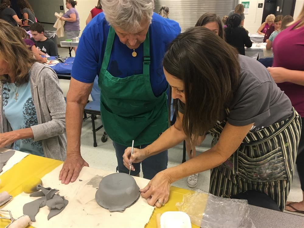 art teacher helping adult make a bowl
