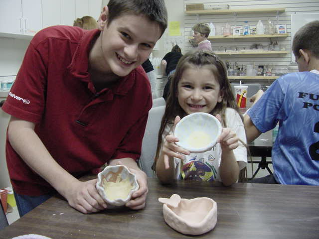 Kids holding bowls they made