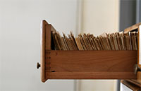 Open filing cabinet drawer filled with papers