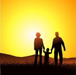 Two parents walking with a child at sunset holding hands.