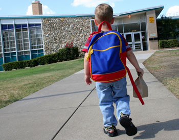 Child walking towards a school holding a lunch bag.