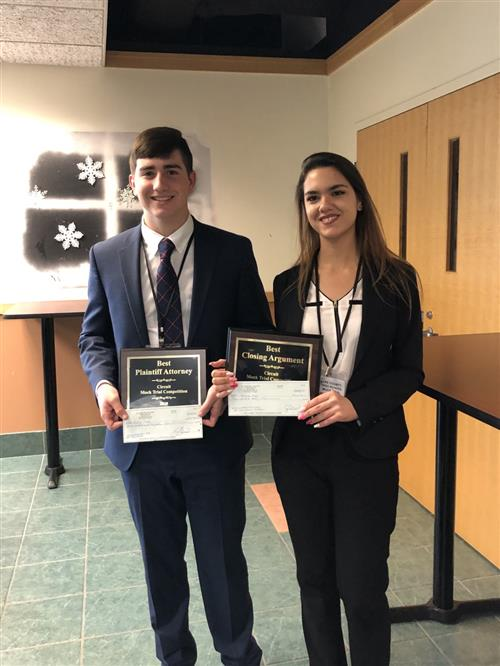 two students posing with awards